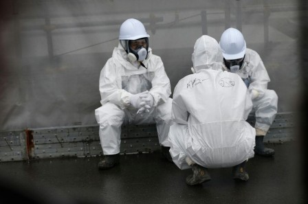 698183-workers-wearing-radiation-protective-gear-rest-on-a-road-at-tepco-s-tsunami-crippled-fukushima-daiic.jpg